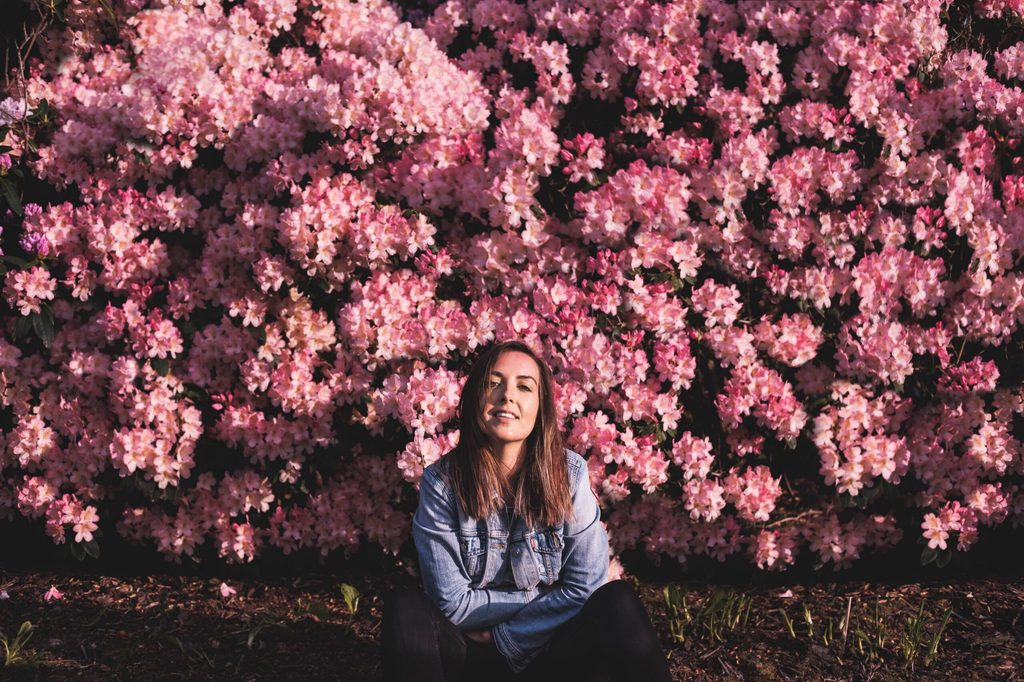 Rachel Jack sitting in the sunshine against a backdrop of pink flowers.