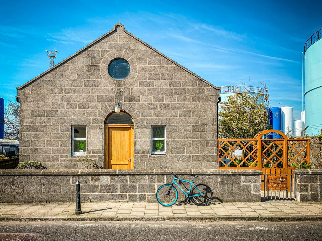 Granite Fittie Community Hall basking in the sunshine, with a blue bicycle in front of it. Markings on front show it was built in 1951.