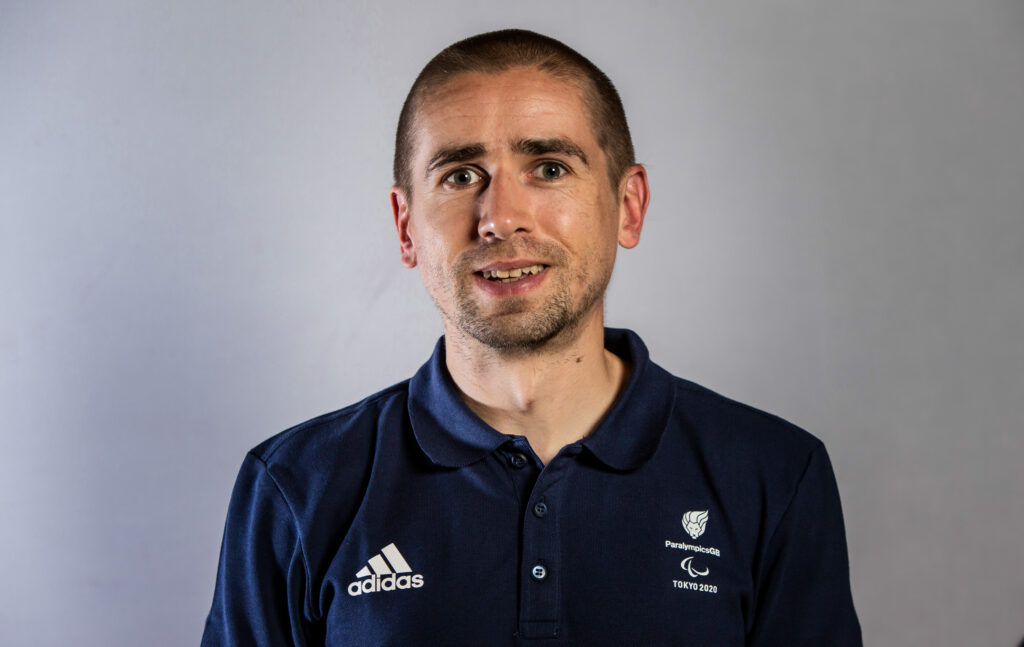 Neil Fachie facing the camera wearing his dark blue Paralympics GB polo shirt. He is smiling.