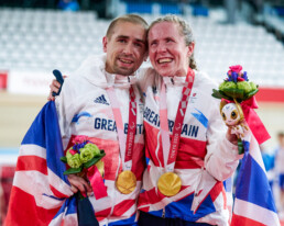 Neil Fachie and Lora Fachie embrace, gold medals round their necks and draped in a union jack flag.