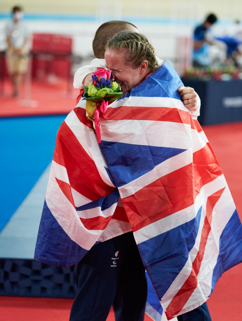 Neil Fachie and Lora Fachie embrace draped in a red, white and blue union jack flag. Lora is crying and holding a bouque of flowers in her hand.