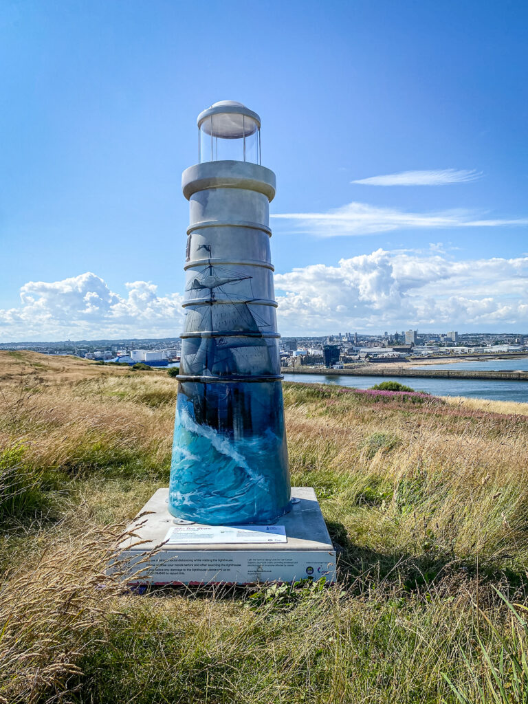Lighthouse sculpture sitting on grass with the Aberdeen skyline and blue skies in the background. Painted on the lighthouse is a sailing ship in heavy seas.