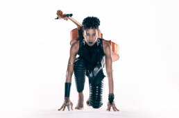 An athletic Ayanna Witter-Johnson on her knees like she was at the start of a race. She has her cello strapped to her back.